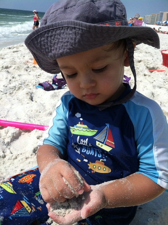 Adik intensely enjoys playing with sand