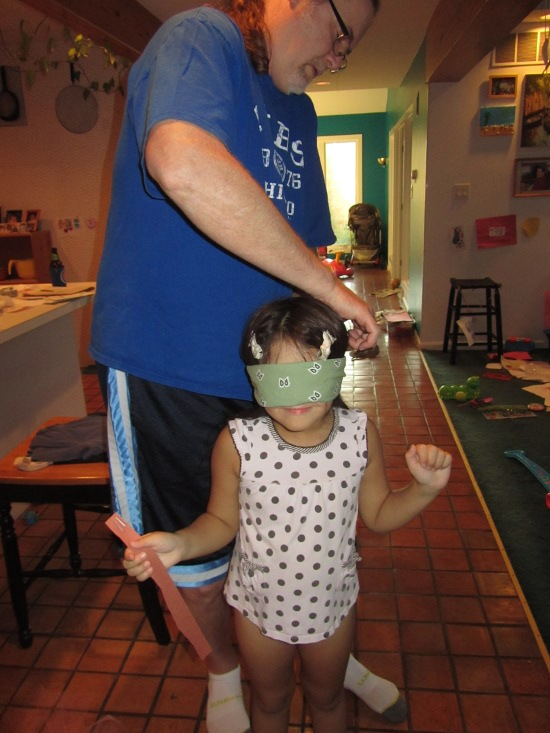 Papa ties on the blindfold