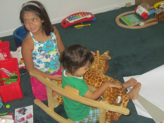 Yaya helps Adik get in this position with Rocky the Rocking Giraffe