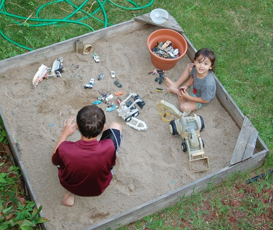 Mason cleared his sandbox and found cars for Adik to play with