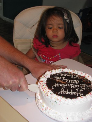 Yaya watches intently as Papa cuts the cake