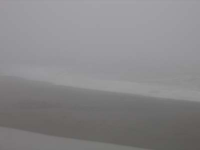 The ocean's edge is completely swallowed up by fog